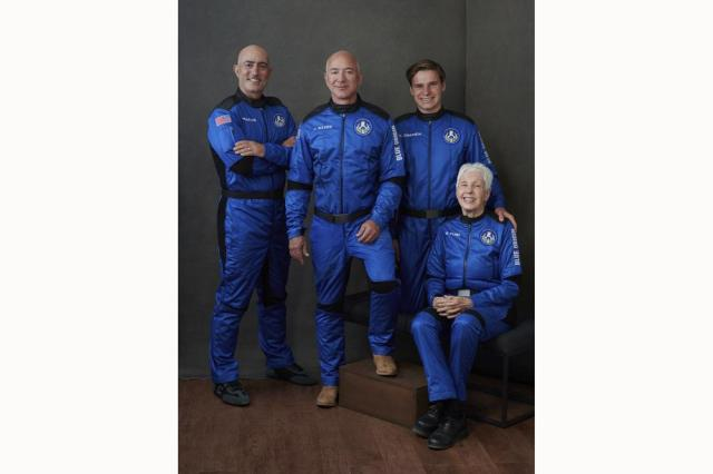 In this photo provided by Blue Origin, from left to right: Mark Bezos, brother of Jeff Bezos; Jeff Bezos, founder of Amazon and space tourism company Blue Origin; Oliver Daemen, of the Netherlands; and Wally Funk, aviation pioneer from Texas, pose for a photo. (Blue Origin via AP)