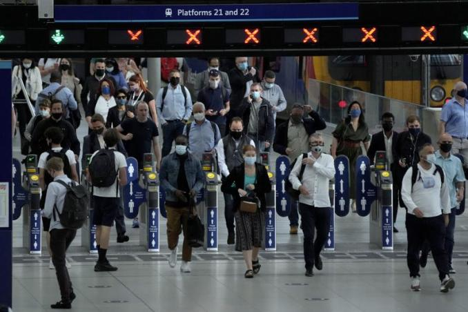 People wear face masks to curb the spread of coronavirus during the morning rush hour at Waterloo train station in London, Wednesday, July 14, 2021. Britain is bracing for acrimony on Monday, July 19 when the government lifts a legal requirement to wear face coverings in most indoor settings, including shops, trains, buses and subways. Donning a mask in many places will stop being an order and become a request. (AP Photo/Matt Dunham)