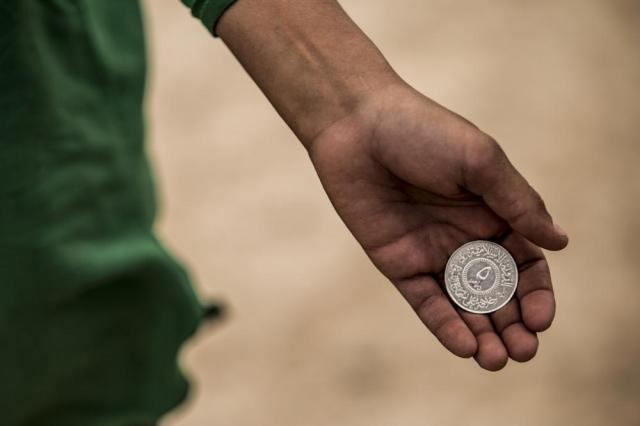 A boy holds shows a 5 dinar Islamic State coin, at al-Hol camp, which houses families of members of the Islamic State group, in Hasakeh province, Syria, Saturday, May 1, 2021.   It has been more than two years that some 27,000 children have been left to languish in al-Hol camp, which houses families of IS members.   Most of them not yet teenagers, they are spending their childhood in a limbo of miserable conditions with no schools, no place to play or develop and seemingly no international interest in resolving their situation.  (AP Photo/Baderkhan Ahmad)