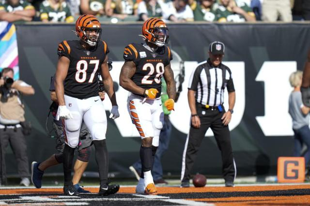 Cincinnati Bengals running back Joe Mixon (28) celebrates with tight end C.J. Uzomah (87) after a touchdown in the second half of an NFL football game against the Green Bay Packers in Cincinnati, Sunday, Oct. 10, 2021. (AP Photo/AJ Mast)