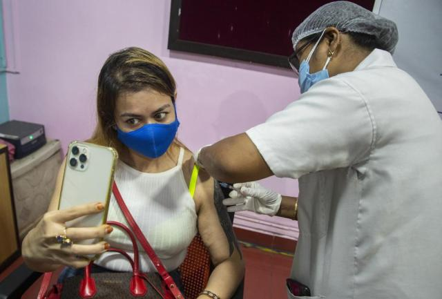 FILE - In this May 17, 2021, file photo, a woman takes selfie as she receives a vaccine for COVID-19 in Gauhati, Assam, India. The disparities of the coronavirus pandemic were already stark in India, where access to health care is as stratified and unequal as other parts of its society. Now, the divide along the lines of wealth and technology are further widening that chasm, and many people are falling through the gaps as vaccines remain inaccessible to millions. (AP Photo/Anupam Nath, File)