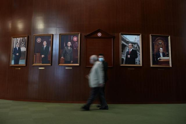 """A pro-China lawmakers walks past portraits of the former presidents of the Legislative Council before the second meeting of """"Improving Electoral System (Consolidated Amendments) Bill 2021"""" at the Legislative Council in Hong Kong Thursday, May 27, 2021. Hong Kong's legislature on Thursday moved closer towards amending electoral laws that would drastically reduce the public's ability to vote for lawmakers and increase the number of pro-Beijing lawmakers making decisions for the city. (AP Photo/Vincent Yu)"""