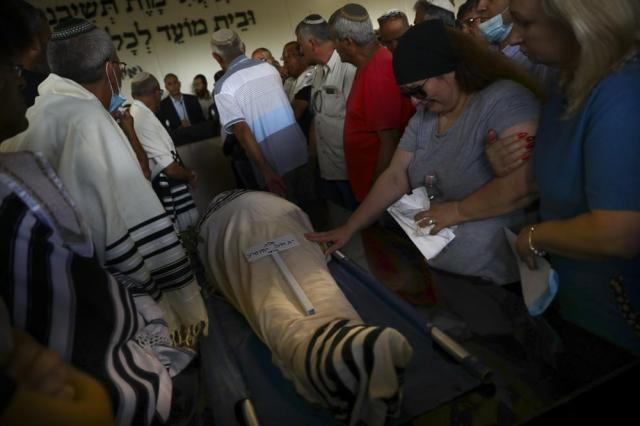 FILE - In this May 18, 2021 file photo, mourners attend the funeral of Yigal Yehoshua, 56, at a cemetery in Hadid, central Israel. Israeli police said Sunday, June 20, 2021, that they have arrested eight Arab suspects in the killing of Yehoshua during a wave of ethnic violence in May. Yehoshua, 56, died after being pelted with rocks during clashes between Arabs and Jews in the mixed city of Lod. (AP Photo/Oded Balilty, File)