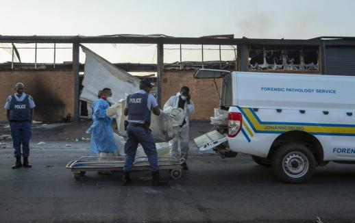 Police officers load bodies of two men that were found inside a burned shop in Johannesburg, South Africa, Sunday, July 11, 2021. Protests have spread from the KwaZulu Natal province to Johannesburg against the imprisonment of former South African President Jacob Zuma who was imprisoned last week for contempt of court. (AP Photo/Themba Hadebe)