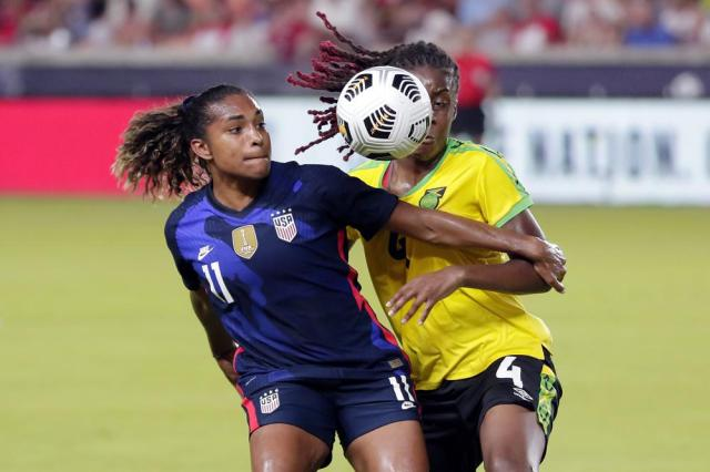 U.S. forward Catarina Macario (11) holds back Jamaica midfielder Vyan Sampson (4) during the first half of their 2021 WNT Summer Series soccer match, Sunday, June 13, 2021, in Houston. (AP Photo/Michael Wyke)
