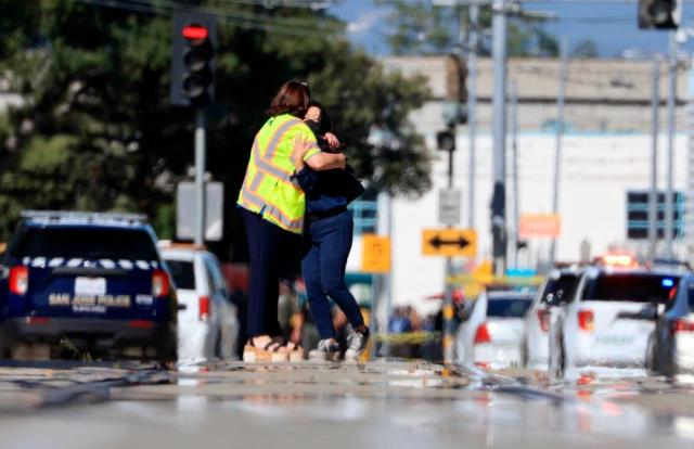 Two people hug on Younger Avenue outside the scene of a shooting in San Jose, Calif., on Wednesday, May, 26. 2021. An employee opened fire Wednesday at a California railyard serving Silicon Valley, killing multiple people before ending his own life, authorities said. The suspect was an employee of the Valley Transportation Authority, which provides bus, light rail and other transit services throughout Santa Clara County, the most populated county in the Bay Area, authorities said. (Randy Vazquez/Bay Area News Group via AP)