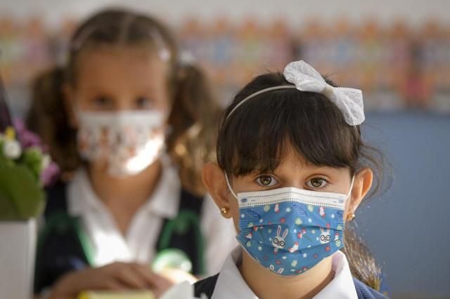 A girl wearing a face mask reacts during festivities marking the beginning of the school year at a school in Bucharest, Romania, Monday, Sept. 13, 2021. Children returned to classrooms in Romania, a country with one of the lowest COVID-19 vaccination rates in the European Union, as the daily infection numbers continue to rise.  (AP Photo/Andreea Alexandru)