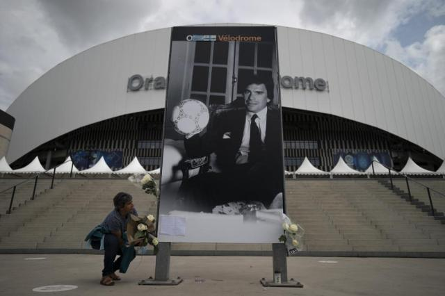 A woman places flowers to Bernard Tapie outside the Orange Velodrome stadium in Marseille, southern France, Sunday, Oct. 3, 2021. Bernard Tapie, the charismatic president of French soccer club Marseille during its glory era whose reign was marred by a match-fixing scandal, has died, Sunday Oct. 3, 2021. He was 78. (AP Photo/Daniel Cole)