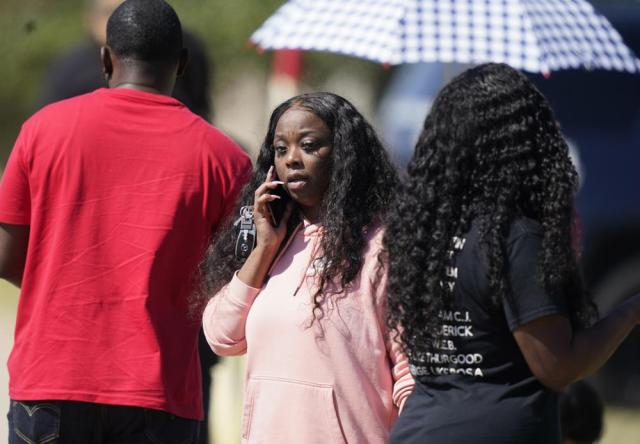 People gather on a road leading to Timberview High School after a shooting at the school in south Arlington, Texas, Wednesday, Oct. 6, 2021. (AP Photo/LM Otero)