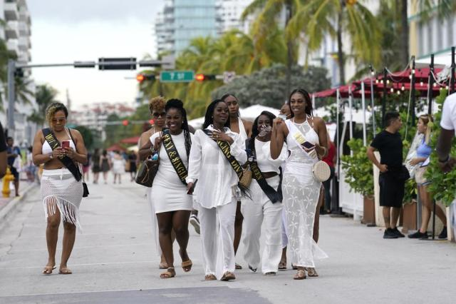 A group of people in a bridal party from Houston, Tx. walk along Ocean Drive, Friday, Sept. 24, 2021, in Miami Beach, Fla. For decades, this 10-block area has been one of the most glamorized spots in the world, made cool by TV shows like Miami Vice, where the sexiest models gathered at Gianni Versace's ocean front estate and rappers wrote lines about South Beach's iconic Ocean Drive. (AP Photo/Lynne Sladky)