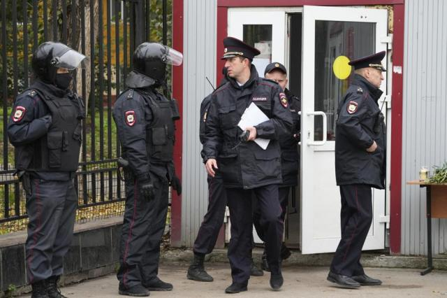 Police gather for a briefing outside the Perm State University following a campus shooting in Perm, about 1,100 kilometers (700 miles) east of Moscow, Russia, Tuesday, Sept. 21, 2021. A student opened fire at the university, leaving a number of people dead and injured, before being shot in a crossfire with police and detained. Beyond saying that he was a student, authorities offered no further information on his identity or a possible motive. (AP Photo/Dmitri Lovetsky)
