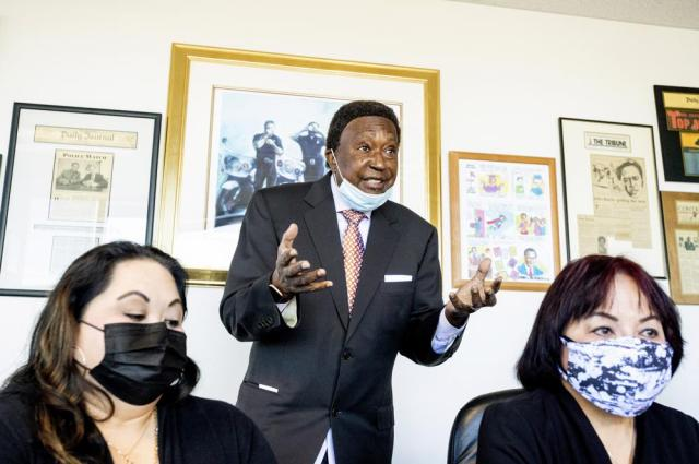 Attorney John Burris discusses the police shooting of Laudemer Arboleda while speaking in his offices on Monday, May 3, 2021, in Oakland, Calif. Seated are Arboleda's mother Jeannie Atienza, right, and sister Jennifer Leong. Danville police officer Andrew Hall faces felony charges for killing Arboleda during a 2018 car chase. (AP Photo/Noah Berger)