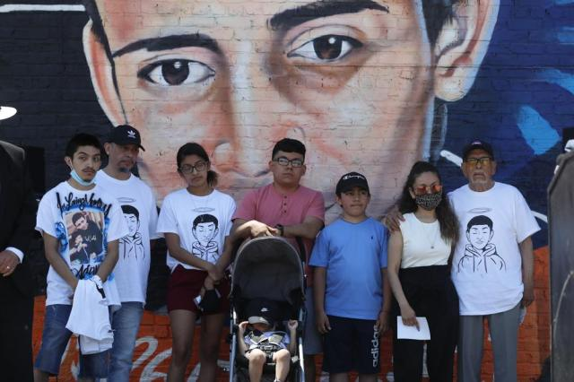 Family members of police shooting victim 13-year-old Adam Toledo stand in front of a mural painted in his honor during a news conference announcing the opening of Adam's Place Inc., a not-for profit organization aiming to help at-risk youth from Chicago and other Midwestern cities to remain out of trouble, Wednesday, May 26, 2021 in Chicago's West Side. (AP Photo/Shafkat Anowar)