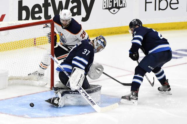 Edmonton Oilers' Leon Draisaitl (29) shoots the puck through the crease by Winnipeg Jets goaltender Connor Hellebuyck (37) during the first overtime period of an NHL hockey Stanley Cup playoff game, Monday, May 24, 2021, in Winnipeg, Manitoba. (Fred Greenslade/The Canadian Press via AP)