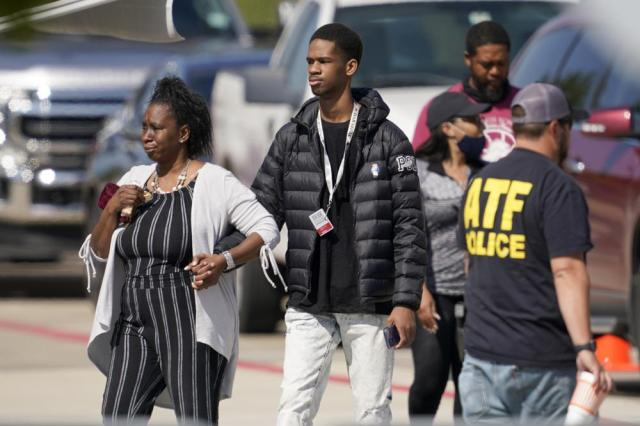 A woman holds the hand of a teenager as they depart the Mansfield ISD Center For The Performing Arts where families were reunited with Timberview High School Students, Wednesday, Oct. 6, 2021 in Mansfield, Texas. Police in Texas have arrested a student suspected of opening fire during a fight at his Dallas-area high school, leaving four people injured. (AP Photo/Tony Gutierrez)