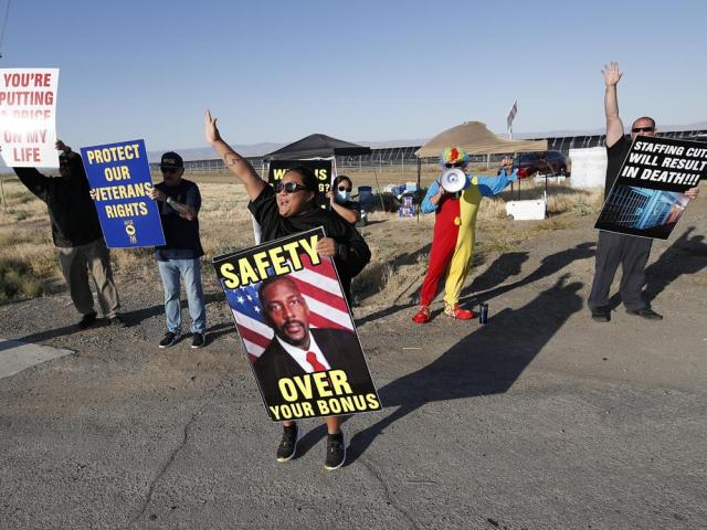 Noni Ahulau, from Honolulu, holding a sign of Warden Douglas K. White, protests staffing shortages at the Federal Correctional Institution at Mendota, Monday, May 17, 2021, near the facility, in Mendota, Calif. (AP Photo/Gary Kazanjian)