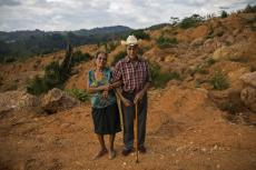 """Alejandro Mejia, 80, and his wife, Petrona Caballero, 80, stand for a portrait at the site of their home destroyed by a landslide triggered by hurricanes Eta and Iota in the village of La Reina, Honduras, Saturday, June 26, 2021. They had been living together here for 48 years. Mejia built his own house. """"I made a wooden box. I threw mud with pine needles on it and let it sun and dry for six days, protecting it from the rain."""" Caballero says, """"In one's own home, one rests one's thoughts. ... I feel a wound, an affliction in my chest. We will suffer from now on."""" (AP Photo/Rodrigo Abd)"""