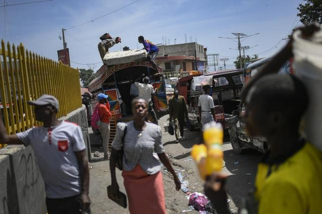 Locals load a mattress on the roof of a bus at the Petion-Ville market in Port-au-Prince, Haiti, Sunday, July 11, 2021, four days after the assassination of Haitian President Jovenel Moise. (AP Photo/Matias Delacroix)