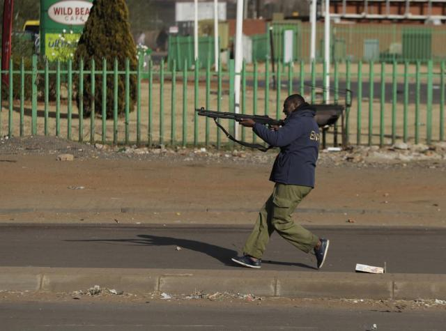 A security man takes aim at looters at a shopping centre in Soweto, Johannesburg, Tuesday July 13, 2021. South Africa's rioting continued Tuesday with the death toll rising to 32 as police and the military struggle to quell the violence in Gauteng and KwaZulu-Natal provinces. The violence started in various parts of KwaZulu-Natal last week when Zuma began serving a 15-month sentence for contempt of court. (AP Photo/Themba Hadebe)