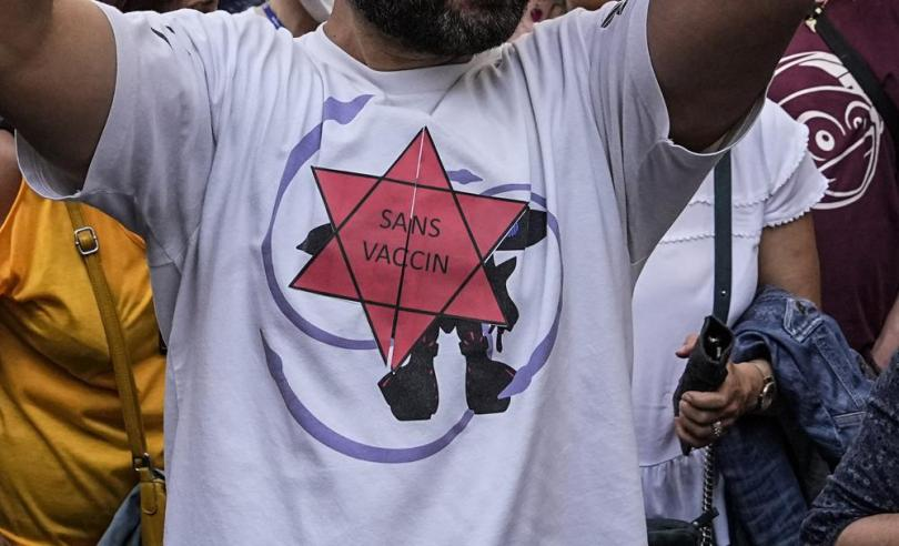 """FILE - In this Saturday, July 17, 2021 file photo, a Star of David reading in French """"without vaccine"""" is attached on a T-shirt of an Anti-vaccine protesters during a rally in Paris. Shouts of """"liberty"""" have echoed through Italian and French streets and squares as thousands show their opposition to plans to require vaccination cards to continue normal social activities, like dining indoors at restaurants, visiting museums or cheering home teams in stadiums. (AP Photo/Michel Euler, File)"""