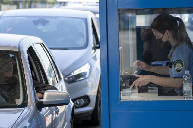 A Croatian border police office inspects travel documents at the border crossing between Croatia and Slovenia, in Bregana, Wednesday, June 2, 2021. The European Union wants to revamp Europe's ID check-free travel area after coronavirus restrictions placed new strains on tourism and business travel throughout the bloc. (AP Photo/Darko Bandic)