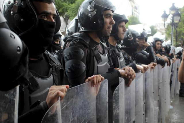 Police attend a gathering of protesters demonstrating against Tunisian President Kais Saied in Tunis, Tunisia. Sunday, Oct. 10, 2021. Thousands of people demonstrated in Tunisia's capital Sunday against the president's seizure of powers in July and other moves seen as threatening the country's democratic gains since the Arab Spring. (AP Photo/Hassene Dridi)