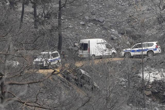 """Police gather near an abandoned van on Troodos mountain, in Ora village, southwestern Cyprus, Sunday, July 4, 2021. Cyprus search crews discovered the bodies of four people outside a fire-swept mountain village on Sunday in what a government minister called the """"most destructive"""" blaze in the east Mediterranean island nation's history. (AP Photo/Petros Karadjias)"""