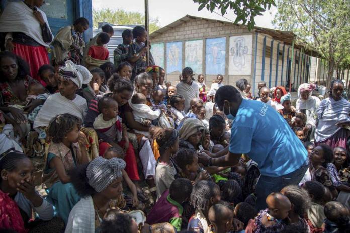 """Joseph Senesie, spécialiste de la nutrition de l'UNICEF, dépiste la malnutrition chez les enfants à Adikeh, dans le district de Wajirat, dans la région du Tigré, dans le nord de l'Éthiopie, lundi 19 juillet 2021. Pendant des mois, les Nations Unies mettent en garde contre la famine au Tigré et maintenant des documents internes et des témoignages révèlent les premiers décès de faim depuis que le gouvernement éthiopien a imposé en juin ce que l'ONU appelle """"un blocus de facto de l'aide humanitaire"""". (Christine Nesbitt/UNICEF via AP)"""