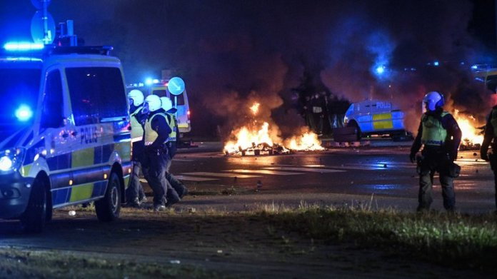 Riot police on the scene as smoke billows from burning tires and fireworks, as a few hundred protesters riot in the Rosengard neighbourhood of Malmo, Sweden, Friday, Aug. 28, 2020. Far-right activists burned a Quran in the southern Swedish city of Malmo, sparking riots and unrest after more than 300 people gathered to protest, police said Saturday. Rioters set fires and threw objects at police and rescue services Friday night, slightly injuring several police officers and leading to the detention of about 15 people. (TT News Agency via AP)