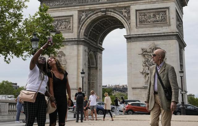 FILE - In this June 17, 2021, file photo, people take a selfie with the Arc de Triomphe in the background at the Champs Elysees avenue in Paris. Countries across Europe are scrambling to accelerate coronavirus vaccinations to outpace the spread of the delta variant in a high-stakes race to prevent hospital wards from filling up again with patients fighting for their lives. (AP Photo/Michel Euler, File)