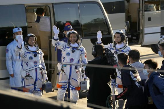 Chinese astronauts, from left, Liu Boming, Nie Haisheng, and Tang Hongbo wave as they prepare to board for liftoff at the Jiuquan Satellite Launch Center in Jiuquan in northwestern China, Thursday, June 17, 2021. China plans on Thursday to launch three astronauts onboard the Shenzhou-12 spaceship who will be the first crew members to live on China's new orbiting space station Tianhe, or Heavenly Harmony. (AP Photo/Ng Han Guan)