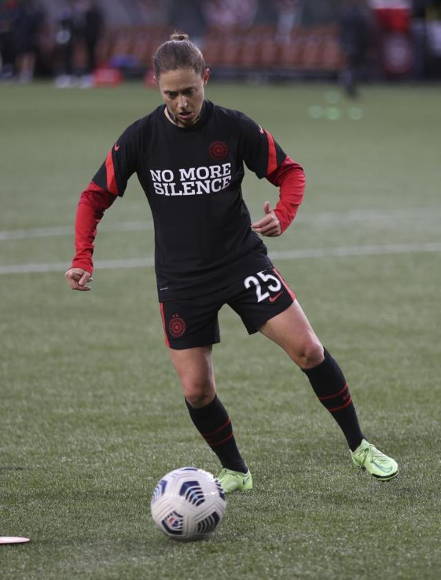 Portland Thorns defender Meghan Klingenberg wears a warmup jersey before the team's NWSL soccer match against the Houston Dash in Portland, Ore., Wednesday, Oct. 6, 2021. Players stopped on the field during the first half of Wednesday night's National Women's Soccer League games and linked arms in a circle to demonstrate solidarity with two former players who came forward with allegations of sexual harassment and misconduct against a prominent coach. (AP Photo/Steve Dipaola)