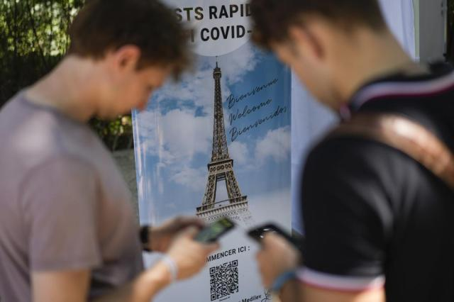 """Visitors register for COVID-19 tests at the Eiffel Tower in Paris, Wednesday, July 21, 2021. Visitors now need a special COVID pass to ride up the Eiffel Tower or visit French museums or movie theaters, the first step in a new campaign against what the government calls a """"stratospheric"""" rise in delta variant infections. (AP Photo/Daniel Cole)"""