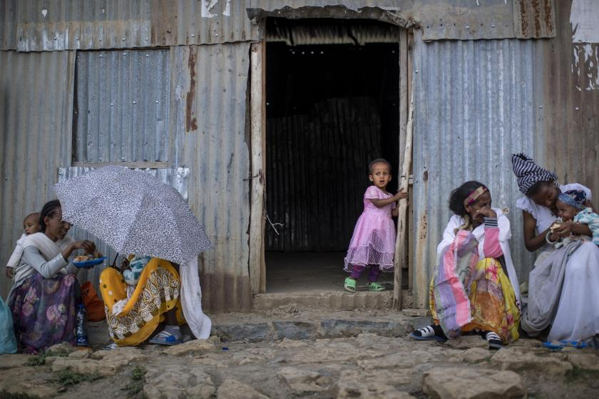 A Tigrayan girl looks out of a doorway as others sit next to a metal shack at a reception center for the internally-displaced in Mekele, in the Tigray region of northern Ethiopia, on Sunday, May 9, 2021. Despite claims by both Ethiopia and Eritrea that they were leaving, Eritrean soldiers are in fact more firmly entrenched than ever in Tigray, The Associated Press has found. (AP Photo/Ben Curtis)