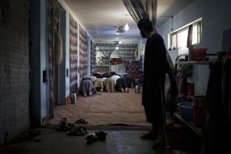 Un grupo de reclusos detenidos recientemente rezan en el penal de Pul-e-Charkhi, en Kabul, Afganistán, el 13 de septiembre de 2021. Pul-e-Charkhi era la principal prisión en la que el gobierno retenía a los talibanes capturados y era conocida por los abusos, las malas condiciones y el hacinamiento, con miles de reos entre sus muros. Ahora, tras hacerse con el control del país, el Talibán gestiona también el penal, que alberga a alrededor de 60 personas, en su mayoría drogadictos y delincuentes acusados. (AP Foto/Felipe Dana)