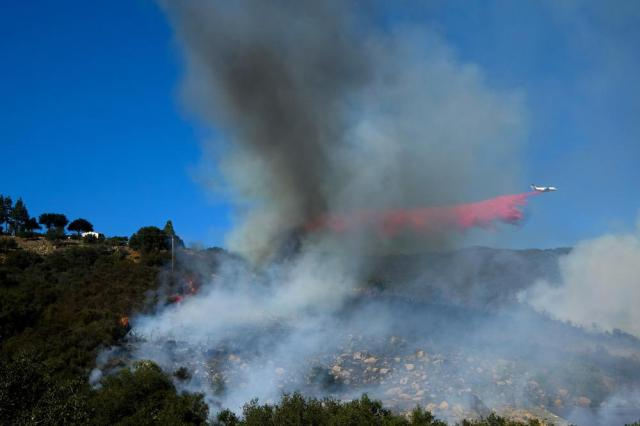 An air tanker drops retardant on a wildfire burning near a home Wednesday, Oct. 13, 2021, in Goleta, Calif. A wildfire raging through Southern California coastal mountains threatened ranches and rural homes and kept a major highway shut down Wednesday as the fire-scarred state faced a new round of dry winds that raise risk of infernos. (AP Photo/Ringo H.W. Chiu)