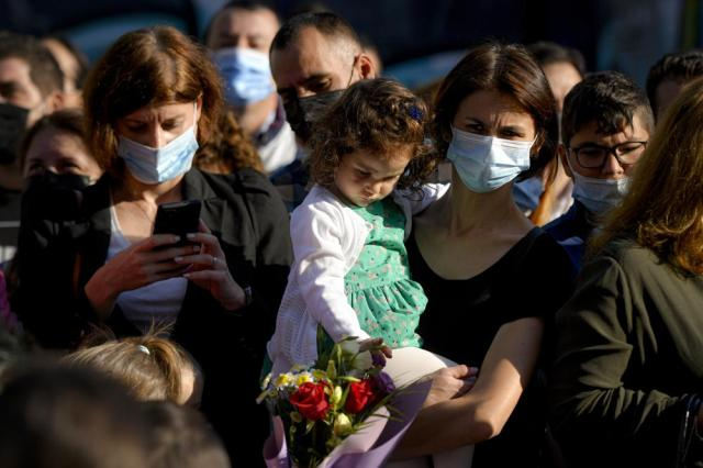 A woman wearing a face mask holds a little girl during festivities marking the beginning of the school year at a school in Bucharest, Romania, Monday, Sept. 13, 2021. Children returned to classrooms in Romania, a country with one of the lowest COVID-19 vaccination rates in the European Union, as the daily infection numbers continue to rise.  (AP Photo/Andreea Alexandru)