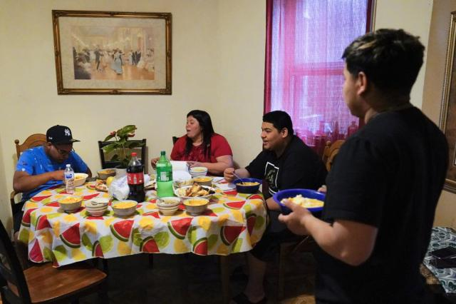 """Keldy Mabel Gonzales Brebe, 37, sits for lunch with her sons, from left, Mino Zuniga Gonzales, 19, Erick Zuniga Gonzales, 17, and Alex Zuniga Gonzales, 21, in the Kensington section of Philadelphia, Sunday, May 16, 2021. Gonzales Brebe, a 37-year-old Honduran immigrant, and her two teenage sons are trying to rebuild their lives together after they were separated under a former """"zero-tolerance"""" policy to criminally prosecute adults who entered the country illegally. (AP Photo/Matt Rourke)"""