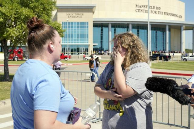 Stephanie Wade, left, comforts her daughter Keeley after she became emotional describing the environment during a school shooting at the Timberview High School in Arlington to the media, after the pair were reunited, Wednesday, Oct. 6, 2021 in Mansfield, Texas. (AP Photo/Tony Gutierrez)