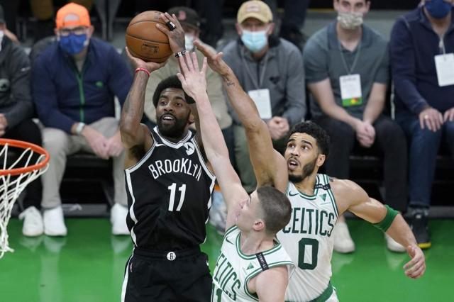Brooklyn Nets guard Kyrie Irving (11) goes up for a shot against Boston Celtics forward Jayson Tatum (0) and Celtics guard Payton Pritchard (11) in the first half of Game 4 during an NBA basketball first-round playoff series, Sunday, May 30, 2021, in Boston. (AP Photo/Elise Amendola)