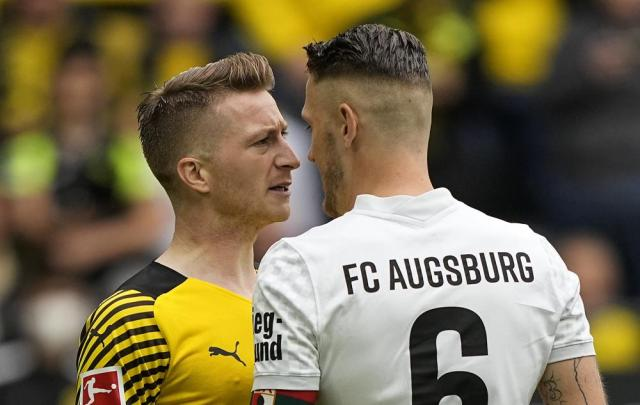 Augsburg's Jeffrey Gouweleeuw, right, and Dortmund's Marco Reus come face to face during the German Bundesliga soccer match between Borussia Dortmund and FC Augsburg in Dortmund, Germany, Saturday, Oct. 2, 2021. (AP Photo/Martin Meissner)
