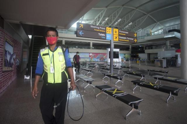 An airport worker walks at the arrival hall of International Ngurah Rai Airport in Bali, Indonesia, Thursday, Oct. 14, 2021. The Indonesian resort island of Bali welcomed international travelers to its shops and white-sand beaches for the first time in more than a year Thursday - if they're vaccinated, test negative, hail from certain countries, quarantine and heed restrictions in public. (AP Photo/Firdia Lisnawati)