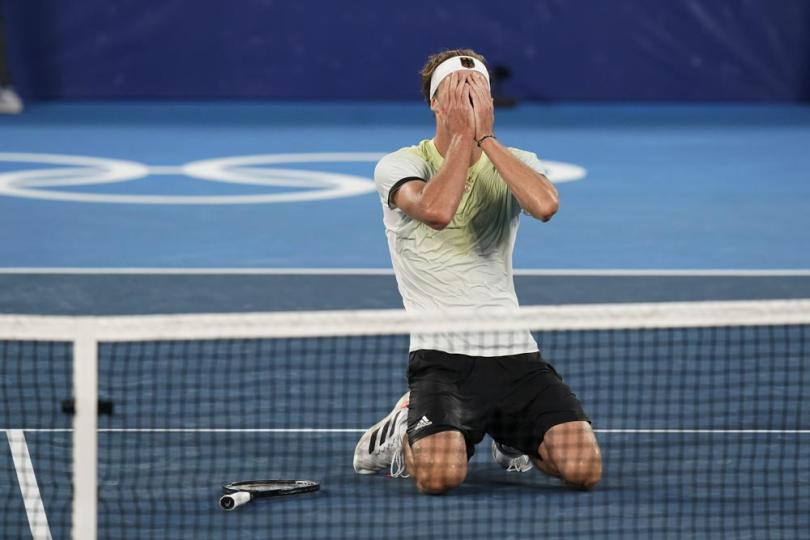 Alexander Zverev, of Germany, reacts after winning the men's single gold medal match of the tennis competition against Karen Khachanov, of the Russian Olympic Committee, at the 2020 Summer Olympics, Sunday, Aug. 1, 2021, in Tokyo, Japan. (AP Photo/Patrick Semansky)