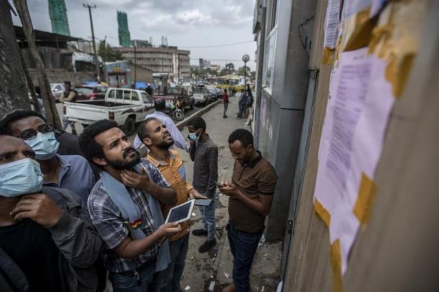 FILE - In this Tuesday, June 22, 2021 file photo, Ethiopians look at electoral results posted on the wall outside a polling station in the capital Addis Ababa, Ethiopia, a day after the country voted in a general election. Ethiopia's ruling Prosperity Party was declared on Saturday, July 10, 2021 the winner of last month's national election in a landslide, assuring a second term for Prime Minister Abiy Ahmed. (AP Photo/Ben Curtis, File)