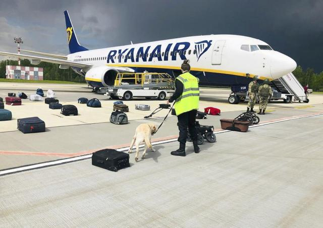 In this photo provided by ONLINER.BY, security use a sniffer dog to check the luggage of passengers on the Ryanair plane with registration number SP-RSM, carrying opposition figure Raman Pratasevich which was traveling from Athens to Vilnius and was diverted to Minsk after a bomb threat, in Minsk International airport, Sunday, May 23, 2021, in BelarusWestern leaders decried the diversion of a plane to Belarus in order to arrest an opposition journalist as an act of piracy and terrorism. The European Union and others on Monday demanded an investigation into the dramatic forced landing of the Ryanair jet. (ONLINER.BY via AP)