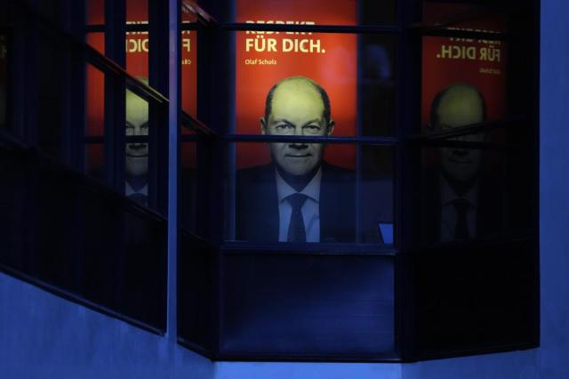 """Social Democratic Party, SPD, candidate for chancellor Olaf Scholz is pictured at a poster that reads: """"Respect For You"""" at the party's headquarters just after German parliament election in Berlin, Sunday, Sept. 26, 2021. (AP Photo/Michael Sohn)"""