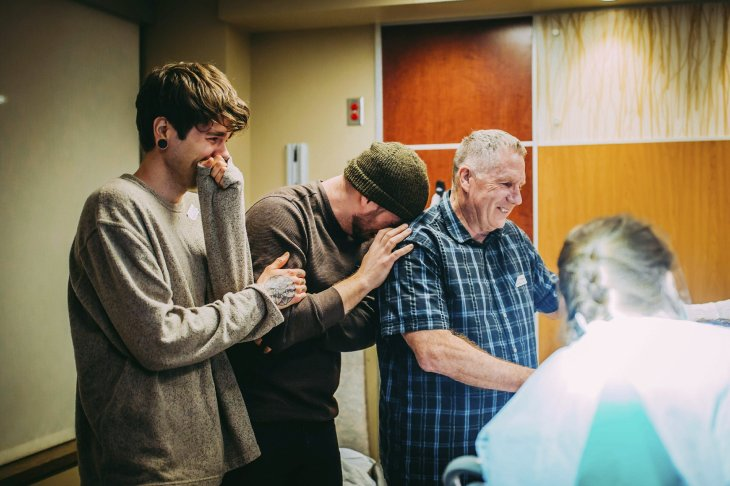 In this March 25, 2019 photo, Elliot Dougherty, left, and his husband Matthew Eledge, second left, react during the delivery of their daughter at the Nebraska Medical Center in Omaha, Neb. Matthew Eledge's mother, Cecile Eledge, volunteered to be the surrogate mother to her grandchild, conceived with sperm from Matthew Eledge and an egg from Dougherty's sister. (Ariel Panowicz via AP)