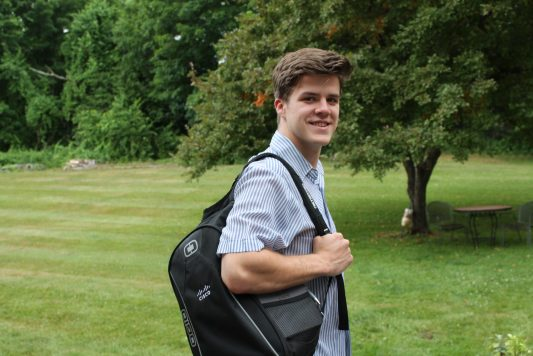 Carl holds a Cisco backpack over his shoulder while standing outdoors.