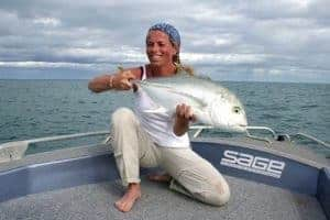 A frontal landscape shot of a woman holding up her catch. She is wearing a High UV Buff® as hair cover. The photo is taken in Far North Queensland so it is hot and humid. The boat is a professional fishing charter vessel. It looks as if she has been out fishing all day and is really happy about her catch. Source: flyfishingweipa.com.au Copyright: Permitted to use on our website