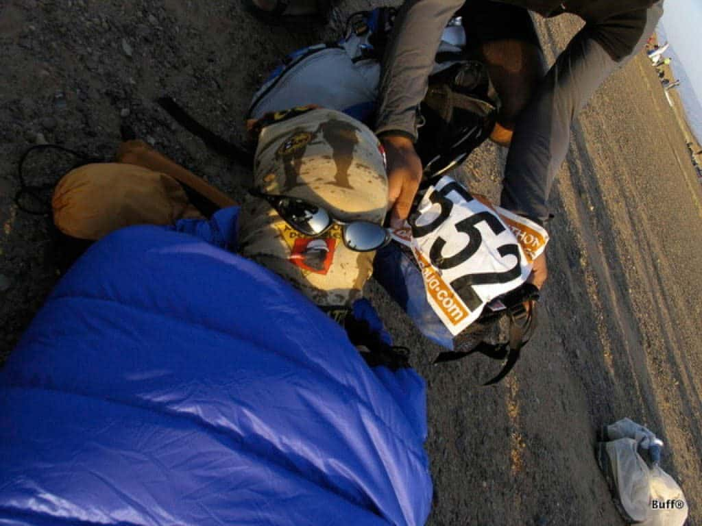 A landscape shot of a person lying on the ground in a sleeping bag. His entire head is covered with a Original Buff®. Another person is kneeling beside his head. He has put sunglasses on the sleeping persons face and is holding up the MDS event number 552. The photo was shot during the 2004 Marathon Des Sables. This is one way how to keept spiders and scorpions out during your sleep. Source: buff.eu © Distributed for the promotion of the Original Buff®